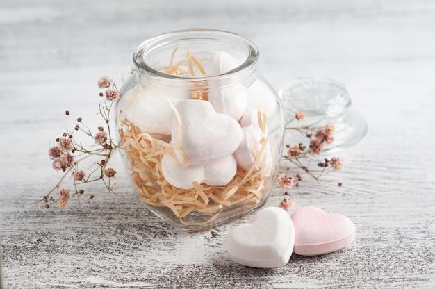 Kompozycja spa z sercami bomb do kąpieli i suchymi kwiatami na rustykalnej ścianie w stylu monochromatycznym. zabiegi kosmetyczne i relaksacyjne