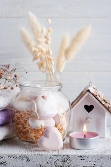Kompozycja spa z sercami bomby do kąpieli i suchymi kwiatami na rustykalnym tle w stylu monochromatycznym. świece i ręczniki. zabiegi kosmetyczne i relaksacyjne
