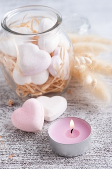Kompozycja spa z sercami bomby do kąpieli i suchymi kwiatami na rustykalnym tle w stylu monochromatycznym. świece i sól. zabiegi kosmetyczne i relaksacyjne