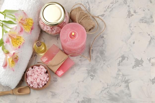 Kompozycja spa z solą morską, olejkami aromatycznymi i ręcznie robionym mydłem na szarym i białym betonie