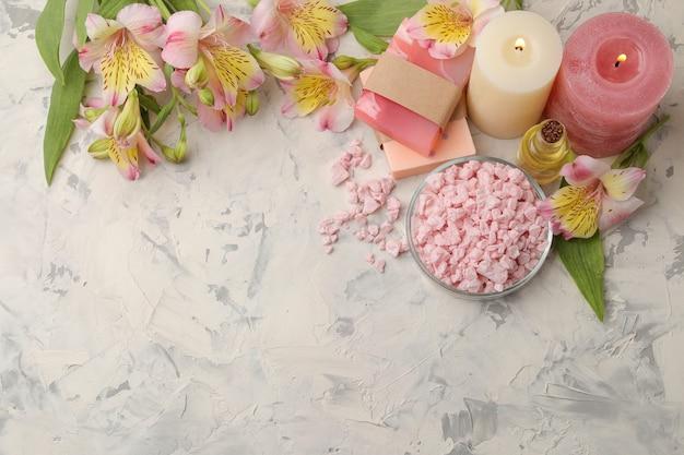 Kompozycja spa z solą morską, olejkami aromatycznymi i ręcznie robionym mydłem z kwiatami. koncepcja spa. na jasnym tle. z miejscem na napis. widok z góry