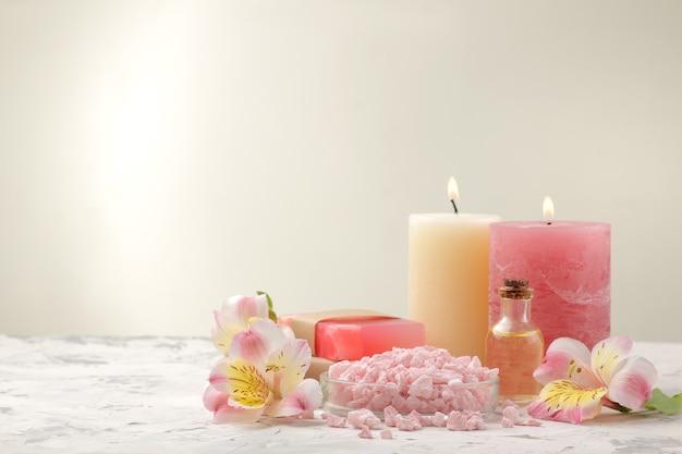 Kompozycja spa z solą morską, olejkami aromatycznymi i ręcznie robionym mydłem z kwiatami. koncepcja spa. na jasnym tle. z miejscem na napis