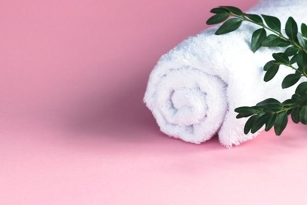 Kompozycja spa z zielonymi liśćmi i białym ręcznikiem na różowym tle