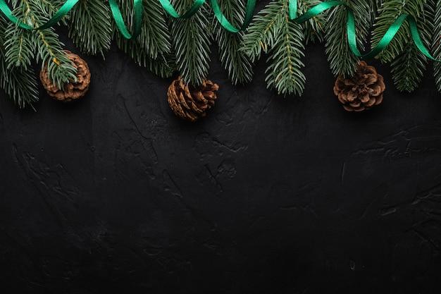 Kompozycja świąt bożego narodzenia z zieloną wstążką, jodłą i szyszkami