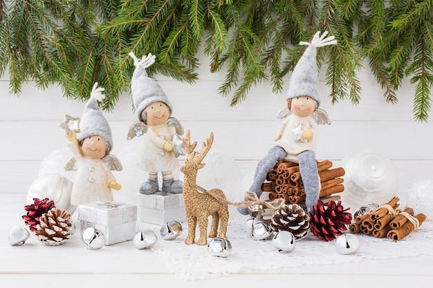 Kompozycja świąteczna. aniołowie, choinka, jeleń na białym drewnianym tle