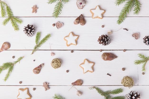 Kompozycja świąteczna. boże narodzenie babeczki z goździkami przypraw, nasion i orzechów, notatnik, długopis, szyszki na drewnianym białym tle. płaski świeckich, widok z góry.