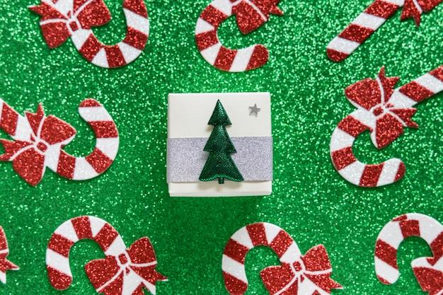 Kompozycja świąteczna. boże narodzenie wzór trzciny cukrowej i pudełko na zielonym błyszczącym tle. wesołych świąt i koncepcji nowego roku.