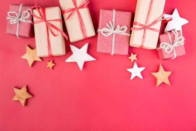 Kompozycja świąteczna. bożenarodzeniowe czerwone dekoracje, gwiazdy i prezenta pudełka na czerwonym tle. leżał płasko, widok z góry, miejsce na tekst