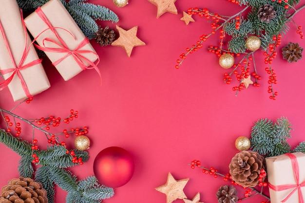 Kompozycja świąteczna. bożenarodzeniowe czerwone dekoracje, jedlinowe gałąź z zabawkami prezenta pudełka na czerwonym tle. leżał płasko, widok z góry, miejsce