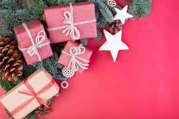 Kompozycja świąteczna. bożenarodzeniowe czerwone dekoracje, jedlinowe gałąź z zabawkami prezenta pudełka na czerwonym tle.