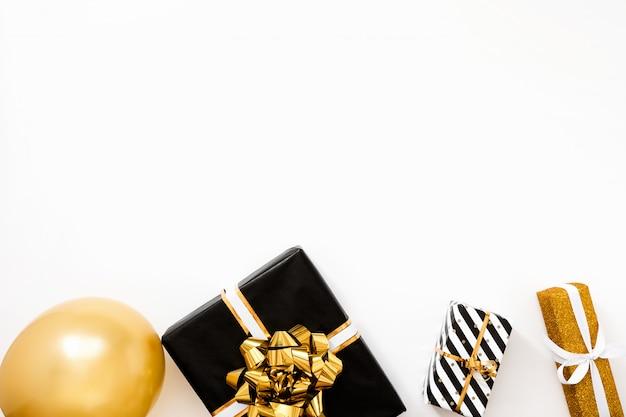 Kompozycja świąteczna. bożenarodzeniowi prezenty, czarny i złoty opakunkowy papier na białym tle