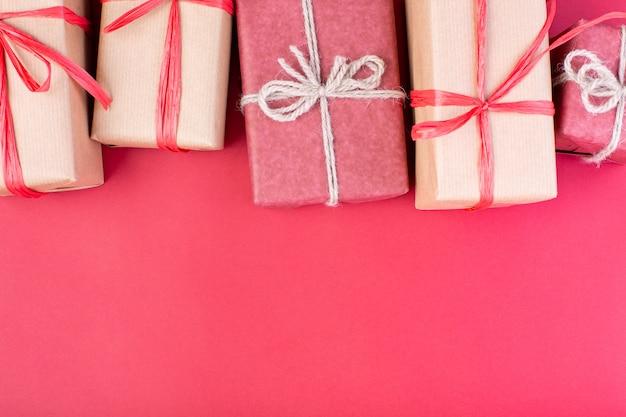 Kompozycja świąteczna. czerwone ozdoby świąteczne, gwiazdki i pudełka na czerwonej ścianie. leżał płasko, widok z góry, miejsce na tekst