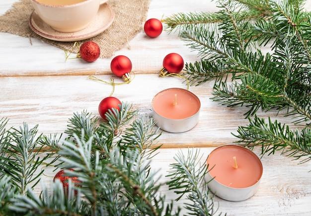 Kompozycja świąteczna. dekoracje, czerwone kulki, gałęzie jodły i świerku, filiżanka kawy, świece na białym drewnianym stole.