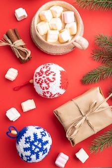 Kompozycja świąteczna. dekoracje, pudełko, cynamon, kulki z dzianiny, gałązki jodły i świerku, filiżanka kawy na czerwonym papierze. leżał na płasko.