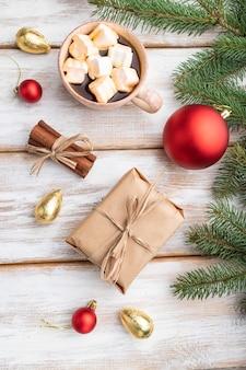 Kompozycja świąteczna. dekoracje, pudełko, czerwone kulki, cynamon, jodła i świerkowe gałęzie, filiżanka kawy na białym drewnianym stole. widok z góry, płaski układ.