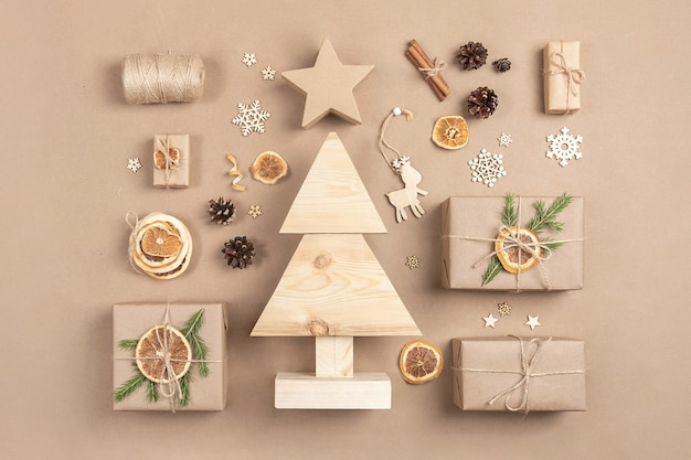 Kompozycja świąteczna. domowe drewniane choinki, prezenty, wystrój wakacje na beżowym tle rzemiosła. koncepcja świąteczna zero odpadów, przyjazna dla środowiska. widok z góry układ płaski.