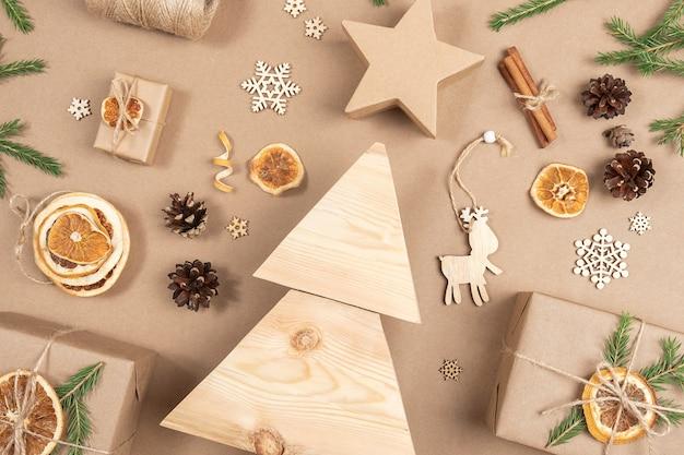 Kompozycja świąteczna. domowe drewniane choinki, prezenty, wystrój wakacje na beżowym tle rzemiosła, zbliżenie. koncepcja świąteczna zero odpadów, przyjazna dla środowiska. widok z góry mieszkanie świeckich miejsca kopiowania.