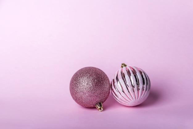 Kompozycja świąteczna. dwa różowe cacko świąteczne, błyszczące kule wiszące na pastelowym tle