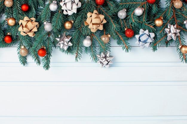 Kompozycja świąteczna, gałęzie choinki ozdobione małymi czerwonymi, złotymi i srebrnymi kulkami.