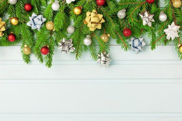 Kompozycja świąteczna, gałęzie choinki ozdobione małymi kulkami oraz kokardkami ze złota i srebra. skopiuj miejsce na jasnoniebieskim tle deski.