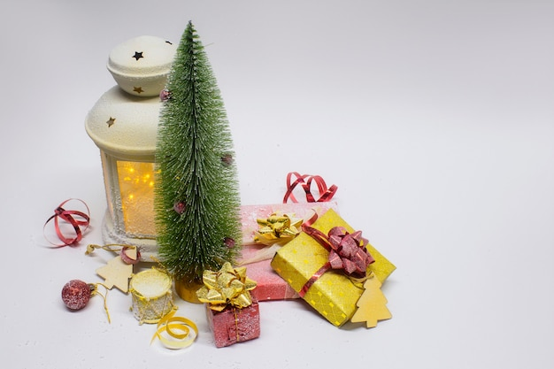 Kompozycja świąteczna i noworoczna. świąteczna świecąca lampka z choinką i dekoracjami, prezentami i jasnymi kokardkami