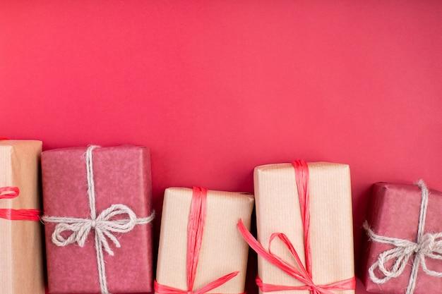 Kompozycja świąteczna, karta z pozdrow. bożenarodzeniowe czerwone dekoracje, gwiazdy i prezenta pudełka na czerwonym tle. leżał płasko, widok z góry, miejsce na tekst