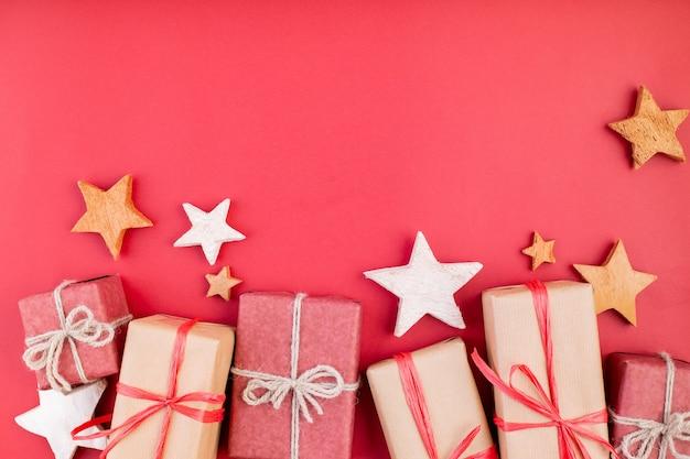 Kompozycja świąteczna, karty z pozdrowieniami. świąteczne dekoracje czerwone, gwiazdki i pudełka na czerwonym tle. leżał z płaskim, widok z góry, miejsce na tekst.