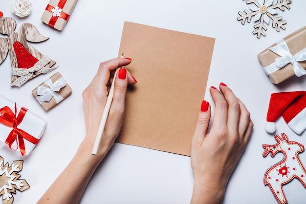 Kompozycja świąteczna. kobiece ręce trzymające ołówek i piszące życzenia świąteczne na kawałku papieru rzemieślniczego z zabawkami sosnowymi i pudełkami na prezenty. widok z góry