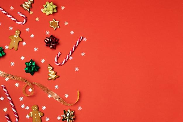 Kompozycja świąteczna leżała płasko, piernik, foremka do ciastek, cukrowa laska, suszona pomarańcza, ozdoby i szyszka na czerwono