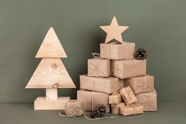 Kompozycja świąteczna lub noworoczna. domowe drewniane choinki, dużo prezent, wystrój świąteczny na zielonym tle. koncepcja świąteczna zero odpadów, przyjazna dla środowiska. widok z przodu miejsce na kopię.