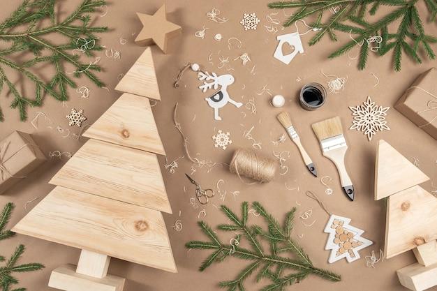 Kompozycja świąteczna lub noworoczna. drewniane choinki, farby, pędzle i gałęzie jodły na beżowym tle rzemiosła. concept zero waste, ekologiczne wesołych świąt. widok z góry układ płaski.