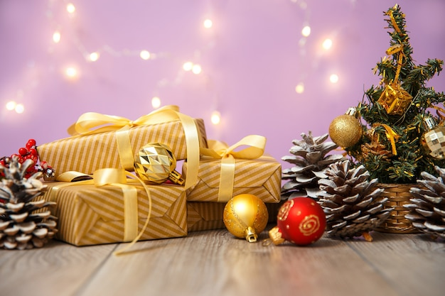 Kompozycja świąteczna lub noworoczna, drewniane różowe tło i złote ozdoby świąteczne i prezenty