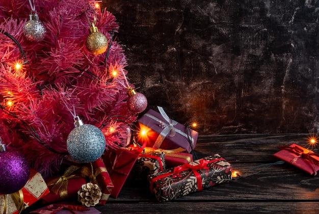 Kompozycja świąteczna lub noworoczna mała różowa choinka na prezentach na czarnym tle
