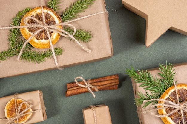 Kompozycja świąteczna lub noworoczna. pudełka ozdobione papierem rzemieślniczym, suszonymi pomarańczami, gałązkami świerkowymi i naturalnym dekorem. concept zero waste, przyjazne dla środowiska wesołych świąt. widok z góry układ płaski.