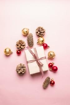 Kompozycja świąteczna lub noworoczna: pudełko z czerwoną wstążką, szyszka, złote i czerwone kulki na różu.