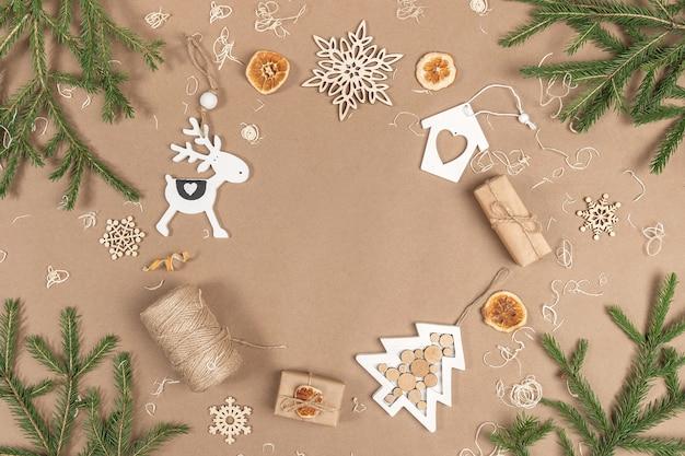Kompozycja świąteczna lub noworoczna. rama, obramowanie wykonane z pudełek, sznurka, dekoracji drewna, suszonych pomarańczy i świerkowych gałązek na beżowym tle rzemieślniczym. koncepcja zero odpadów wesołych świąt miejsca kopiowania.