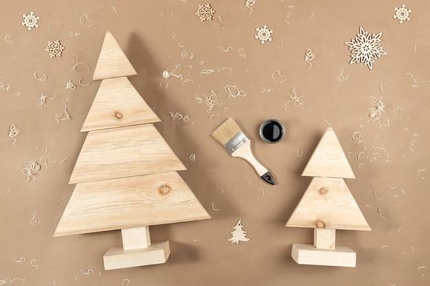 Kompozycja świąteczna lub noworoczna. ręcznie robione drewniane choinki, farby, pędzle na rzemieślniczym beżowym tle.
