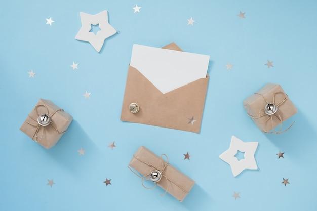 Kompozycja świąteczna lub zimowa z kopertą rzemieślniczą i białymi dekoracjami na pastelowym niebieskim tle. koncepcja nowego roku.