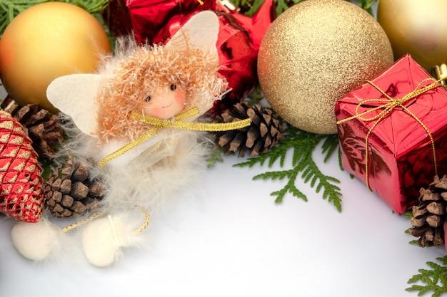 Kompozycja świąteczna na białym prześcieradle z bombkami, szyszkami i aniołami