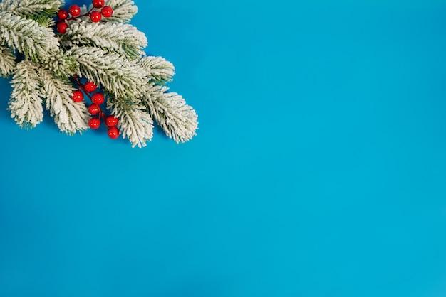 Kompozycja świąteczna na niebieskim tle z drzewa śniegu i czerwonych jagód. widok z góry, miejsce
