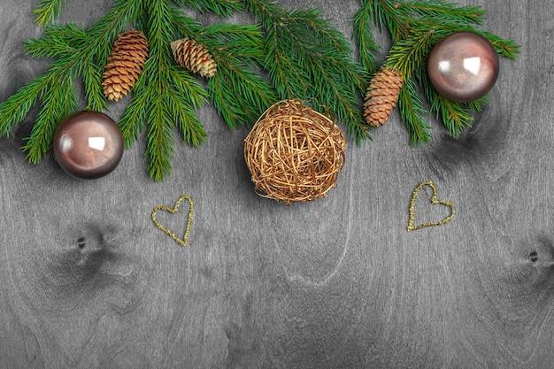 Kompozycja świąteczna na pocztówkę, okładkę, baner. jodła rozgałęzia się i piłki, rożek na nieociosanym drewnianym tle. boże narodzenie, ferie zimowe, koncepcja nowego roku. zamknij się, kopiuj miejsca na tekst.