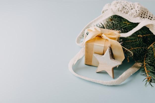 Kompozycja świąteczna. noworoczna lub świąteczna nowoczesna ekologiczna bawełniana siatkowa torba z jodłowymi gałęziami