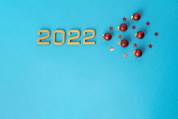 Kompozycja świąteczna numer 2022 czerwone bombki i wzory gwiazdek na niebieskim tle
