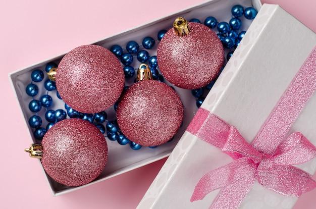 Kompozycja świąteczna. otwarte pudełko z bombkami i niebieską girlandą w pastelowym różu. leżał z bliska. .