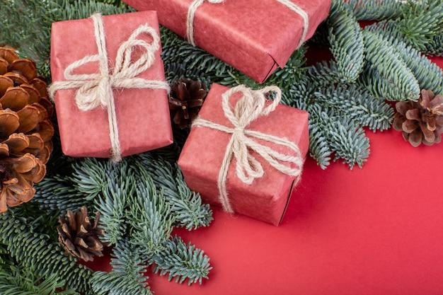 Kompozycja świąteczna. ozdoby choinkowe czerwone, gałęzie jodły z pudełkami zabawek na czerwonej powierzchni. leżał płasko, widok z góry, miejsce