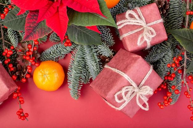 Kompozycja świąteczna. ozdoby choinkowe czerwone, gałęzie jodły z pudełkami zabawek na czerwonej ścianie. leżał płasko, widok z góry, miejsce