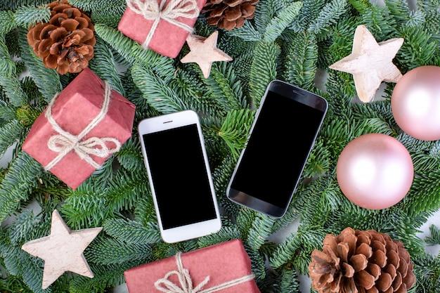 Kompozycja świąteczna. ozdoby choinkowe, gałęzie jodły z pudełkami na zabawki i smartfony. kartka z życzeniami. leżał płasko, widok z góry, miejsce