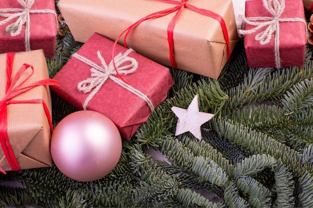 Kompozycja świąteczna. ozdoby choinkowe, gałęzie jodły z pudełkami na zabawki. kartka z życzeniami.