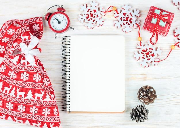 Kompozycja świąteczna. ozdoby choinkowe, girlanda, zegar, jeleń, prezent i pusty notatnik na białym tle drewnianych.