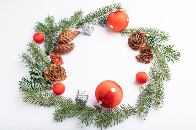 Kompozycja świąteczna. ozdoby, kulki, szyszki, gałęzie jodły i świerku na białym tle.